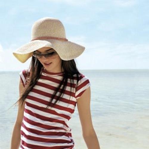девушка в шляпке и солнечных очках на пляже