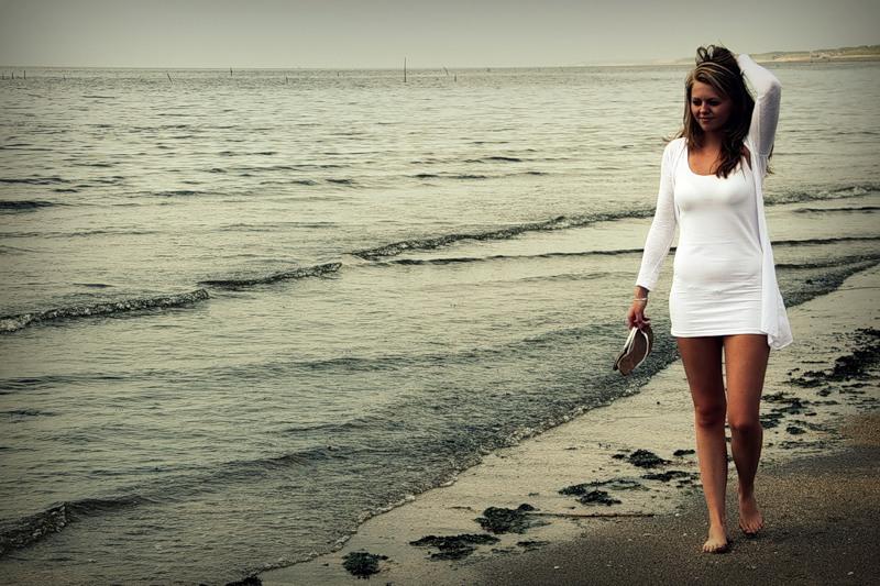 девушка в белом гуляет по берегу моря