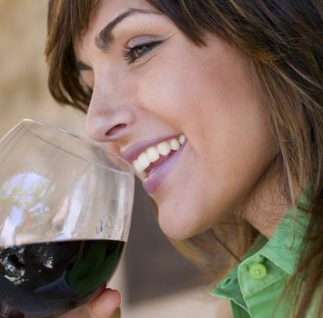 женщина, улыбаясь, пьет вино