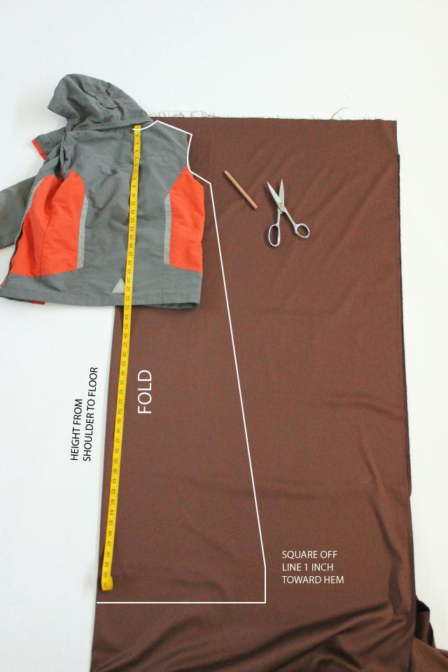 Обрисовываем на ткани половину куртки, удлиняя ее согласно полученной мерке роста плюс 4 см – и уводя при этом линию немного под углом в бок, т. к. низ робы/плаща должен по правилам расширяться