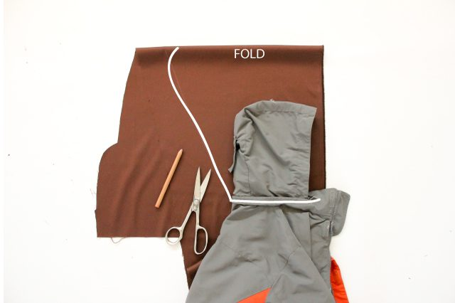Складываем куртку пополам по всей высоте, снова складываем ткань и обрисовываем на ней капюшон, добавляя объем, как показано на снимке
