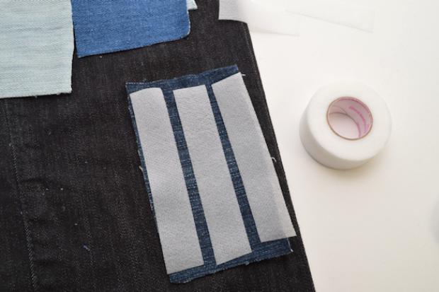 Начинайте наклеивать куски материала на джинсу на клейкую паутинку
