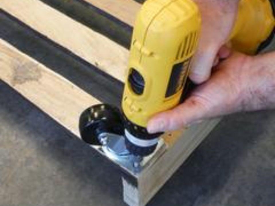 Переверните одну из палет и закрепите ножки-колесики