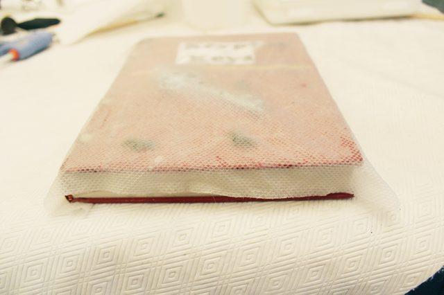 Переверните жесткую основу с влажной бумагой на книгу: бумага должна ровно и без разрывов лечь на обложку с объемными деталями