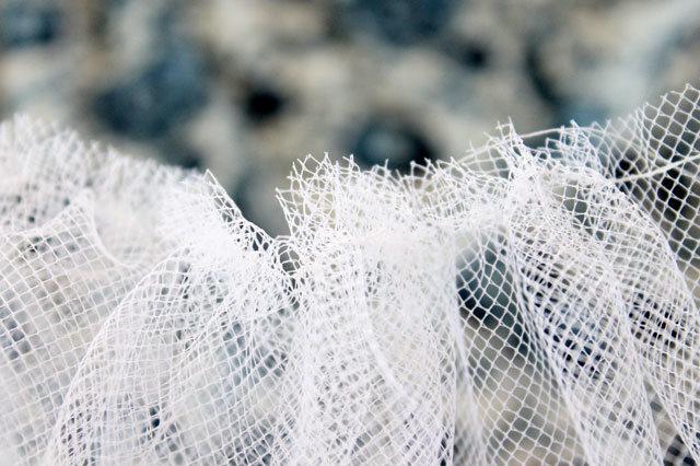 Далее находим нитку, что шла от шпульки, и очень аккуратно постепенно вытягиваем ее из шва вперед, присбирая сетчатую полоску