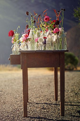 стол, заставленный банкам с полевыми цветами