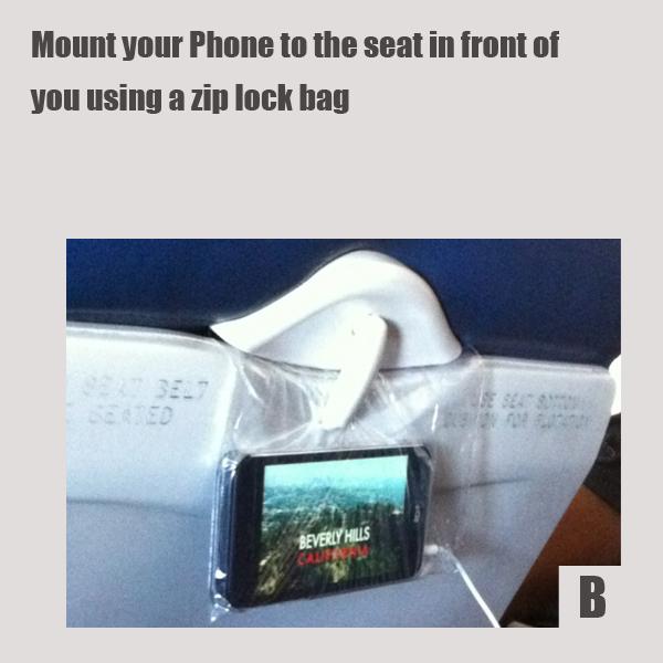 Надоело руками держать смартфон перед собой в самолете? Положите телефон в тонкий небольшой пакет и защемите пакет сверху краем откидного столика.