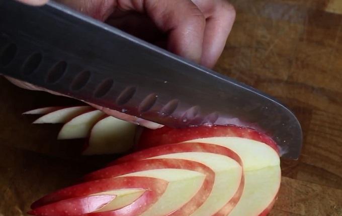 Чтобы было место для вставки головы лебедя, спереди прорезаем в яблоке большой и глубокий прямоугольник