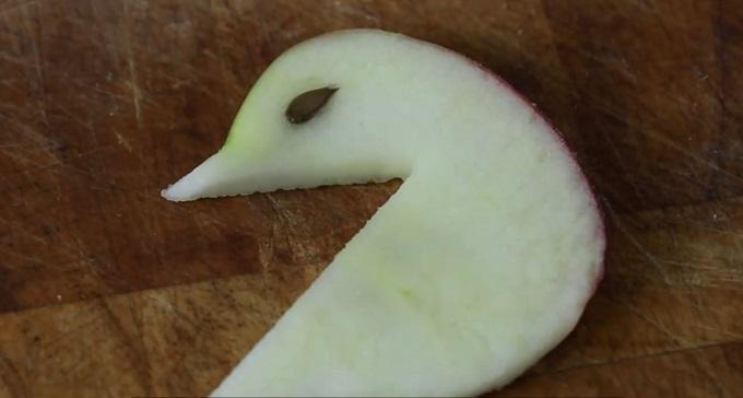 С обеих сторон головы лебедя по очереди определите, где будет располагаться глаз, чуть сковырните мякоть в этом месте и вложите в выемку вместо мякоти яблочное зернышко