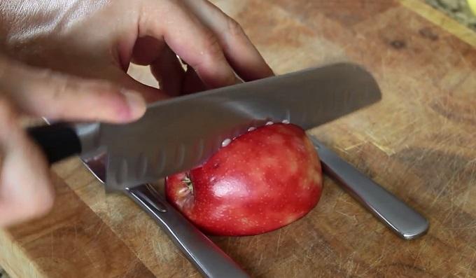 Третьим ножом прорежьте яблоко вертикально - немного сбоку (вправо) от центра до упора вниз – т. е. до лежащих на доске ножей