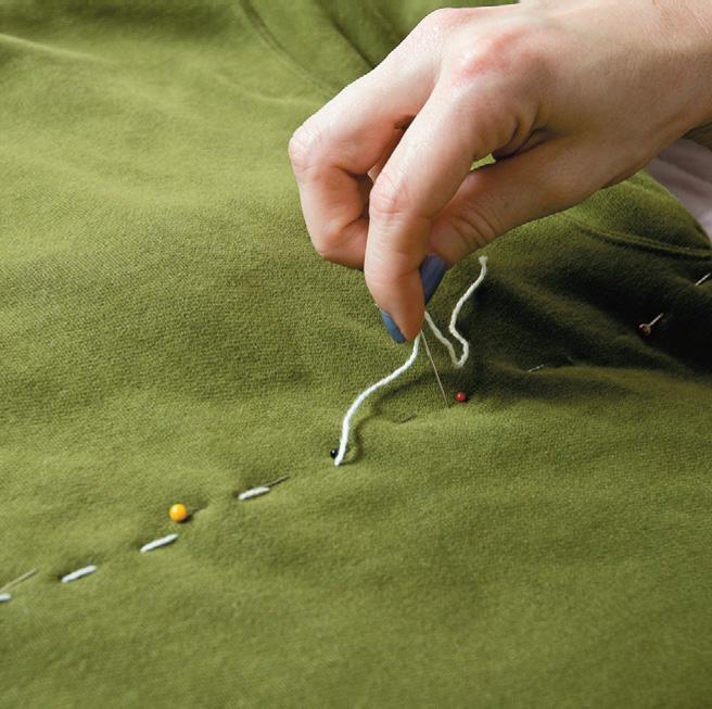 Булавками на глаз наметьте спереди на свитере чуть выгнутую вверх линию от конца левого подмышечного шва до правого