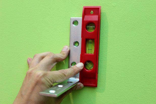 В отверстиях скобы карандашом сделайте пометки на стене