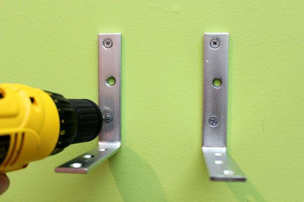 вкрутите шурупы, крепя скобы-кронштейны к стене
