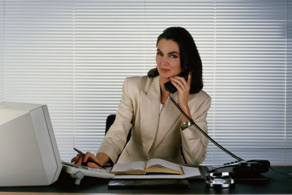 Бизнес-леди отвечате женщина на звонок телефон трубка в руке офис управленец начальник