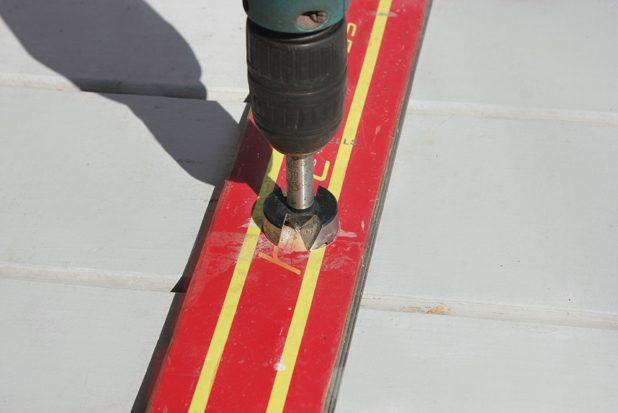 С центром на метках просверливаем углубления специальной насадкой, удерживая дрель ровно под 90 градусов к плоскости лыжи
