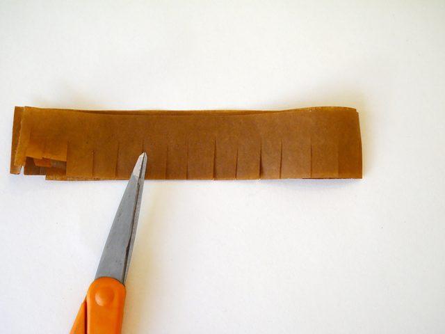 С одной стороны порежьте ножницами эту стопку на бахрому с шагом примерно в 0,6 см
