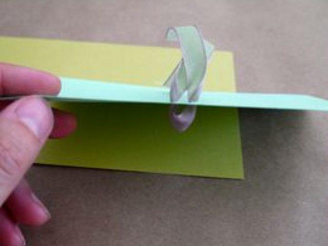С лицевой стороны открытки проденьте оба кончика ленты, каждый в свое отверстие, и подтяните кончики с изнанки