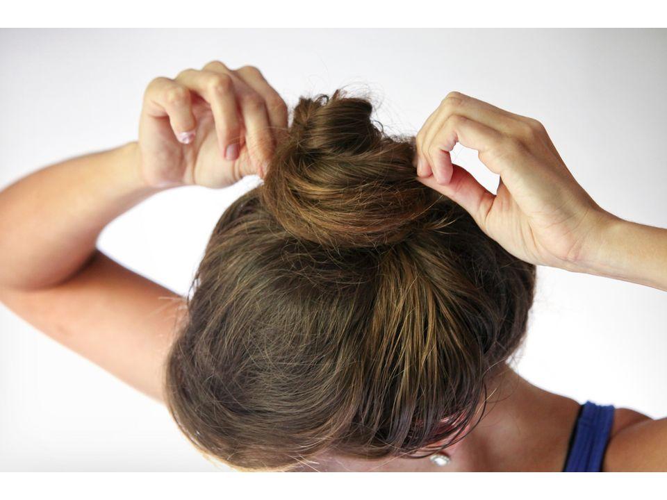 девушка женщина закрутила пучок и заправляет кончики волос под резинку
