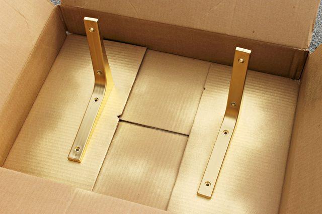 Ставим уголки в коробку и примерно с расстояния 30,5 см опрыскиваем кронштейны полностью золотой краской – тонкими слоями