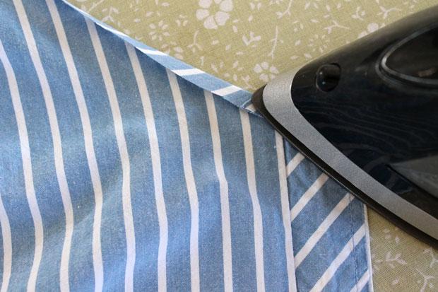 По всей линии выреза спереди и сзади загните ткань на 0,6 см на изнанку и прогладьте
