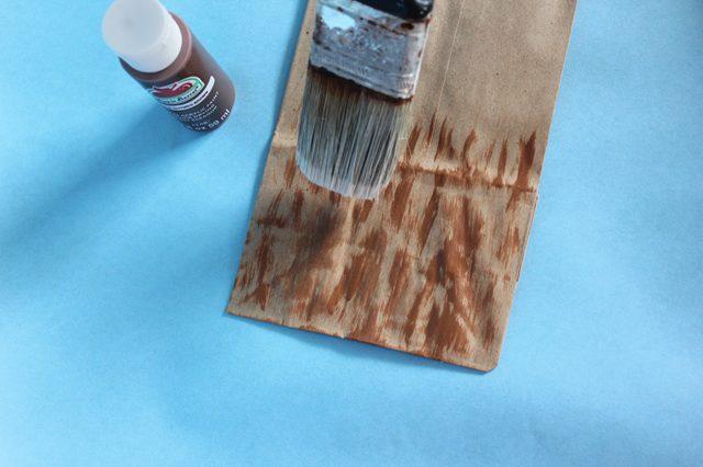 На нижнюю половину каждого первого пакета из двух для метел - на все 4 стороны пакета - наносим коричневым цветом полосы разной длины и ширины, чтобы сымитировать ветки в метле