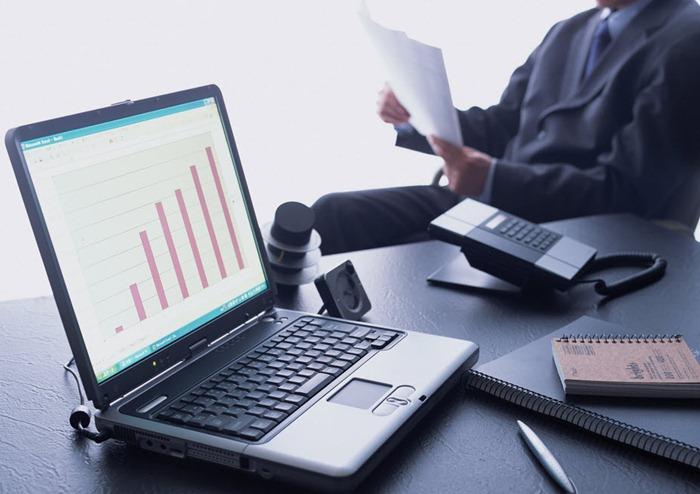 Бизнесмен читает документы, на столе ноутбук, телефон, блокноты. Офис.