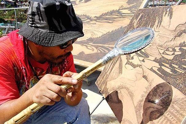 Джордан Манг-Осан (Jordan Mang-osan) выжигает детальные картины лупой по дереву
