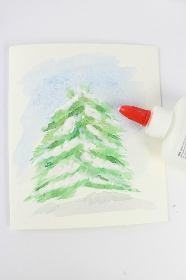 Возьмите белый канцелярский клей, нанесите щедрое его количество на белые зоны на елке