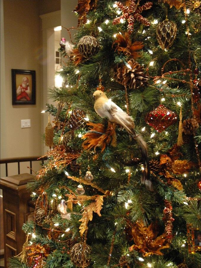 Если вы все-таки больше настроены на градации коричневого, но хотите видеть в доме таки яркую и праздничную елку, добавьте к нему приглушенного золота в игрушках, на ткани и пластиковых гирляндах и листьях