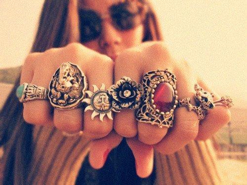 Большое количество украшений - массивные кольца на пальцах