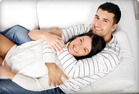 Счастливая молодая пара на диване в обнимку