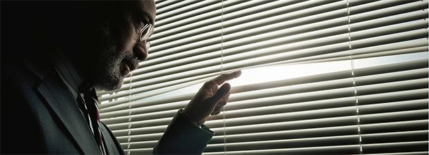 мужчина в костюме, приоткрывая жалюзи, шпионит за происходящим на улице