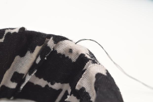 проденьте иглу через ткань с тыльной стороны браслета сверху