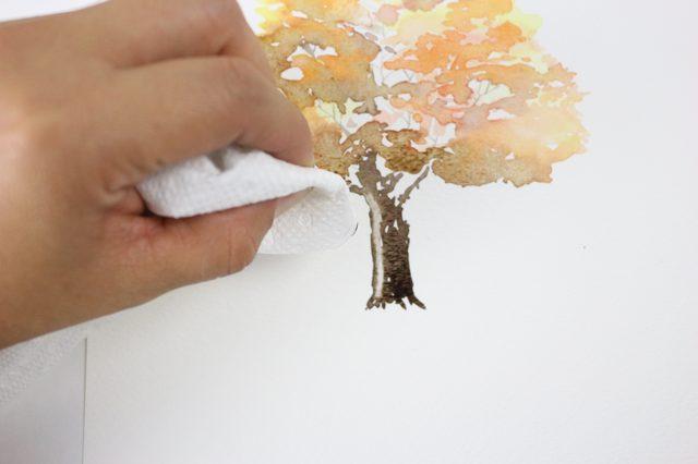 Пока краска на рисунке все еще влажная, возьмите сложенное в полоску бумажное полотенце и уберите немного краски со ствола – из его центра