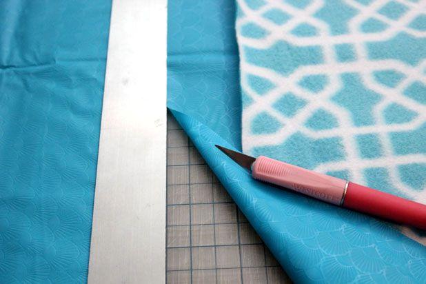 отрежьте винил/клеенку по краю флиса с отступом в 5-6 см, режьте ножом по линейке