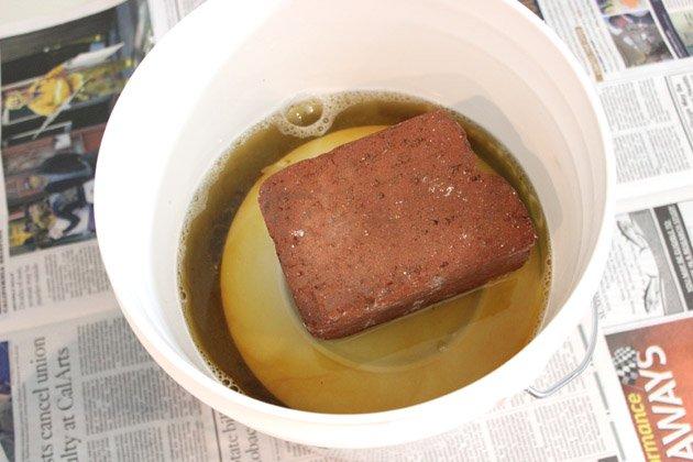 Придавливаем шишки перевернутой керамической или стеклянной тарелкой с кирпичом на ней