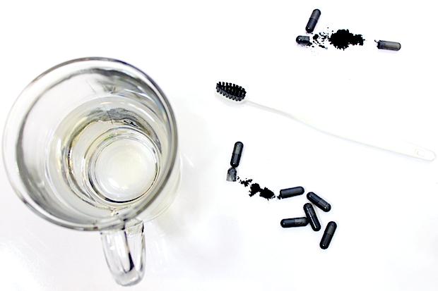вода в стакане и капсулы активированного угля