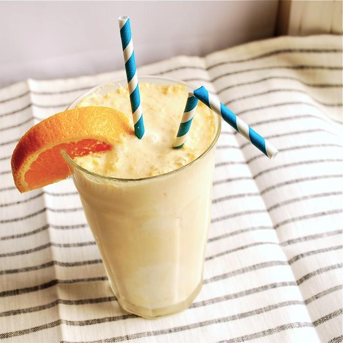 готовая апельсиновая крем-сода в прозрачном бокале с соломинками и долькой апельсина