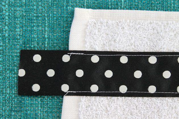 Прямым швом с шагом средней длины пришиваем с обоих длинных краев ленты (с некоторым отступом от этих краев) отрезанный кусок к полотенцу