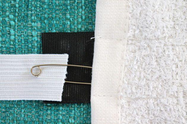Вставляем булавку с кончиком резинки между полотенцем и пришитой лентой