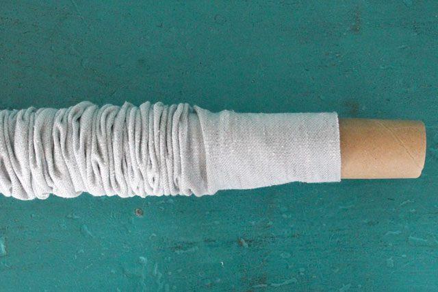 Противоположный – открытый – конец трубы из ткани начинаем натягивать на картонную тубу, собирая ткань в плотные складки на картоне