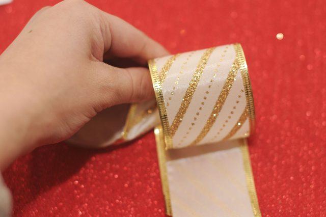 Удерживая сгиб пальцами, из левого – в разы большей длины - кончика ленты сделайте сверху над сгибом круглую петлю