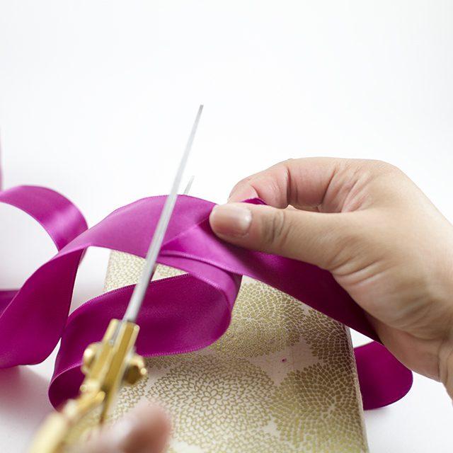 Оберните ленту вокруг подарка по ширине и отрежьте ее ровно столько, чтобы хватило свободно завязать 3-4 узла