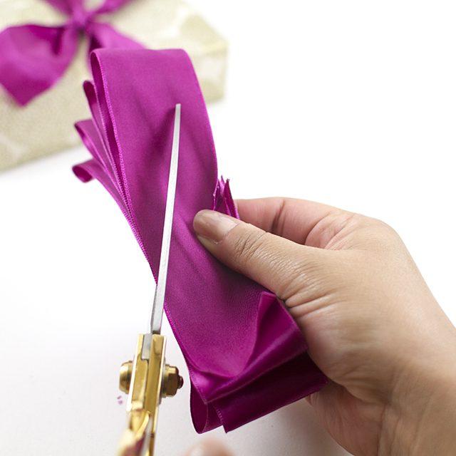 Надежно удерживая стопку из ленты двумя пальцами, ровно по центру относительно длины сделайте на стопке справа и слева разрезы под углом