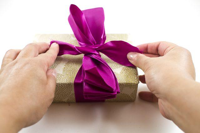Положите центр подрезанной с двух сторон стопки из ленты на узелок на коробке и надежно привяжите стопку к подарку кончиками ленты, оставшимися от того же узла