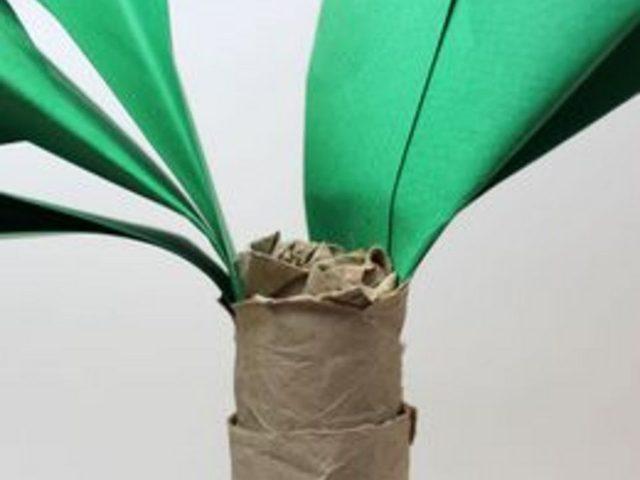 Всуньте скрепленные нижние кончики двух «пучков» пальмовых листьев довольно глубоко внутрь верхнего рулона ствола напротив друг друга