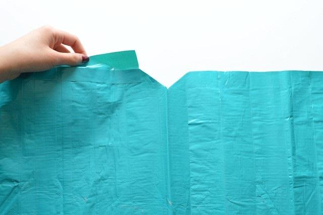По бокам от выреза по верхнему краю горизонтально наклейте полоски скотча