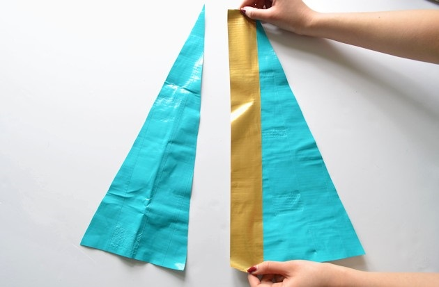 Ровно клейте четверть (по ширине) полоски золотого скотча на один длинный край бирюзового треугольника