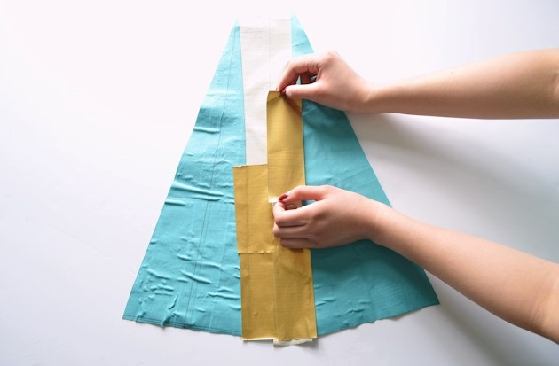 Переворачиваем два склеенных треугольника и посередине между ними наклеиваем небольшие куски  того же золотого скотча