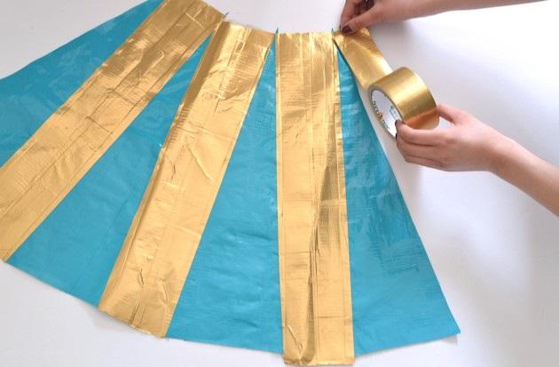родолжаем составлять из бирюзовых треугольников и золотых полосок юбку для платья из скотча и простыни